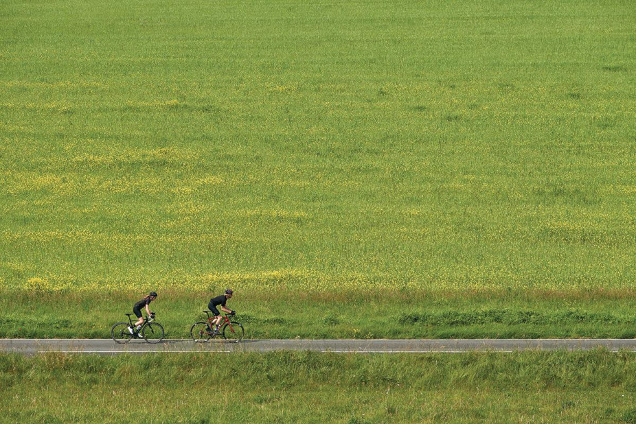 Two cyclists riding a Orro carbon road bike, cycling on a small flat road next to a big green field