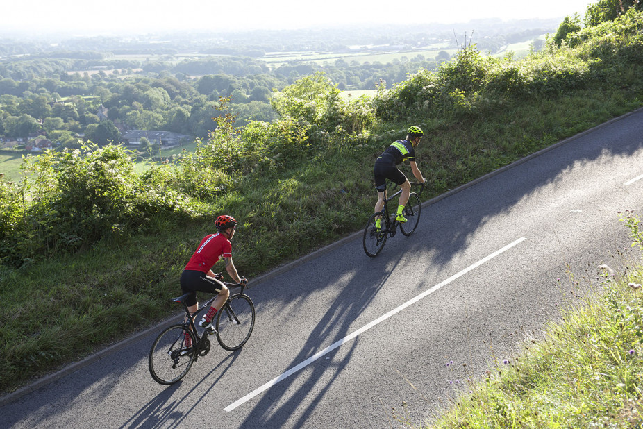Two cyclists riding together on their Orro Bikes up a steep hill on a hot summers day