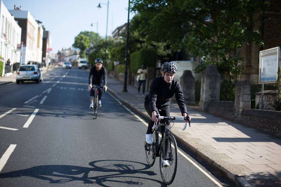 Two cyclists descending down a busy public road riding their Orro Bikes