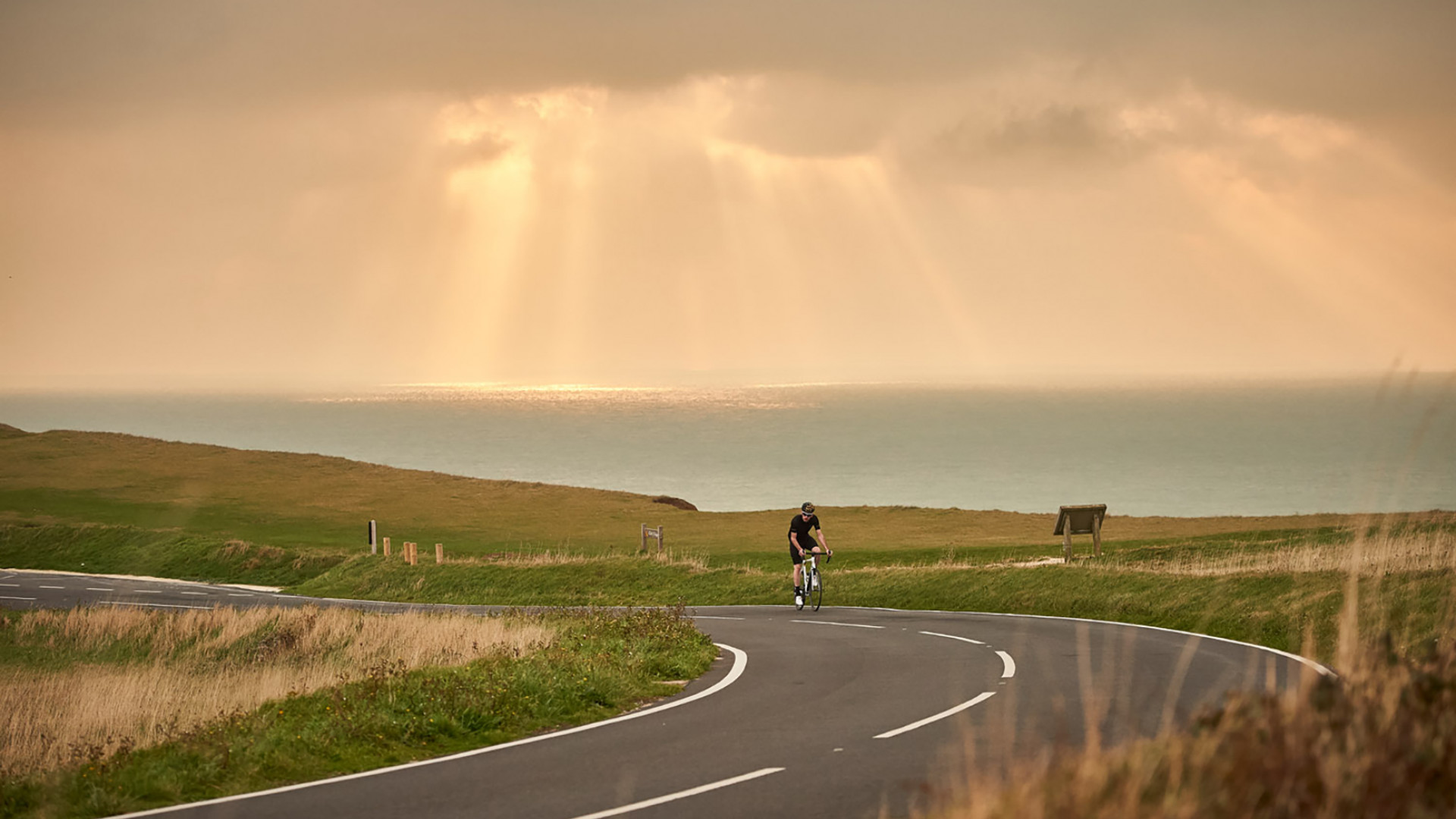 A cyclist riding a Orro Carbon Fibre Road Bike through a seaside coastal road whilst wearing a black Orro Cycling Jersey