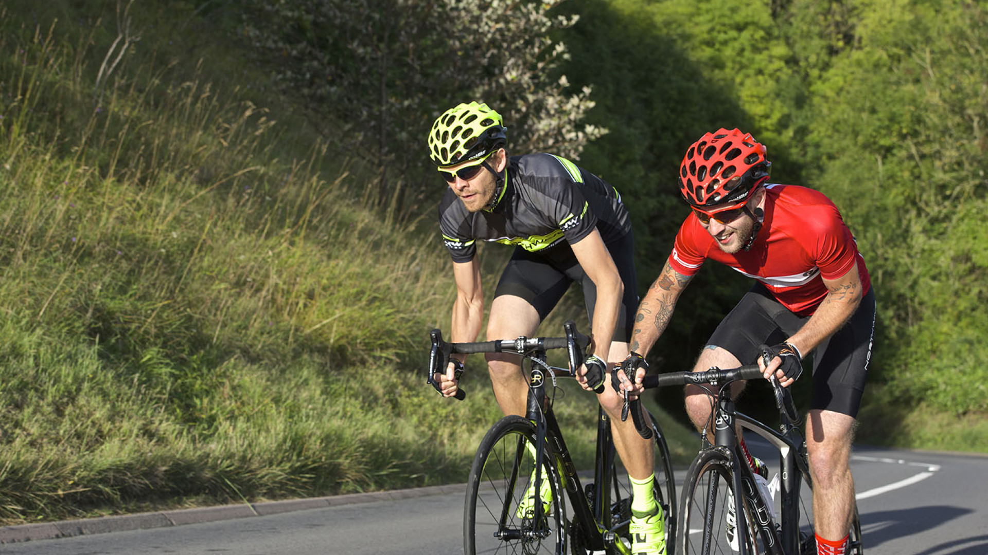 Two cyclists racing up a hill in their Orro carbon fibre road bikes