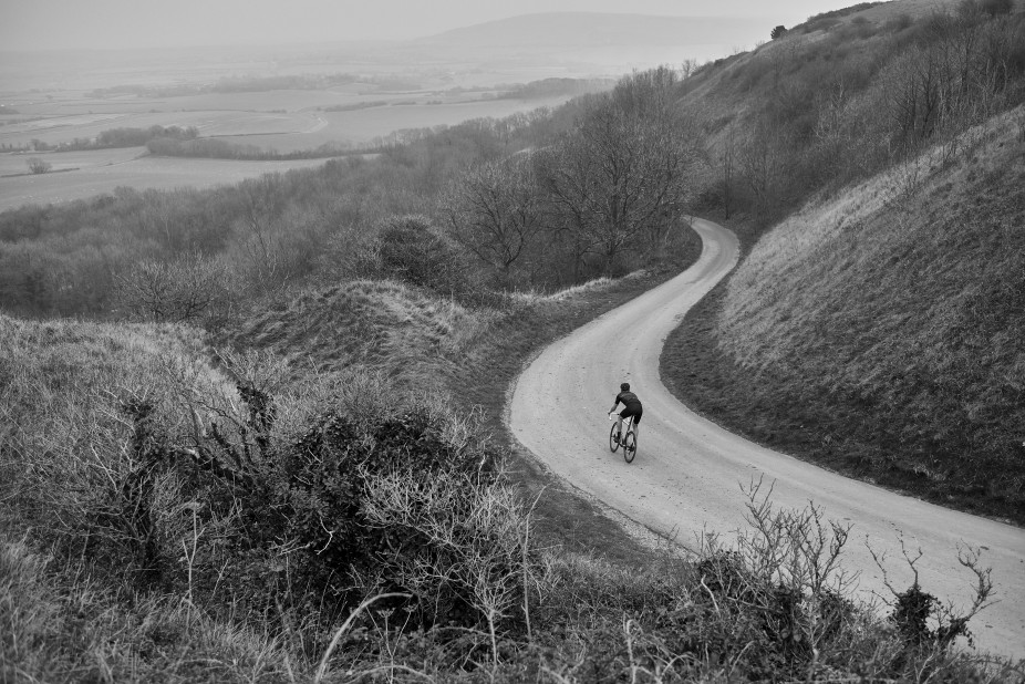 Cyclist sprinting down at full speed down a country road in Ditchling Beacon, England,