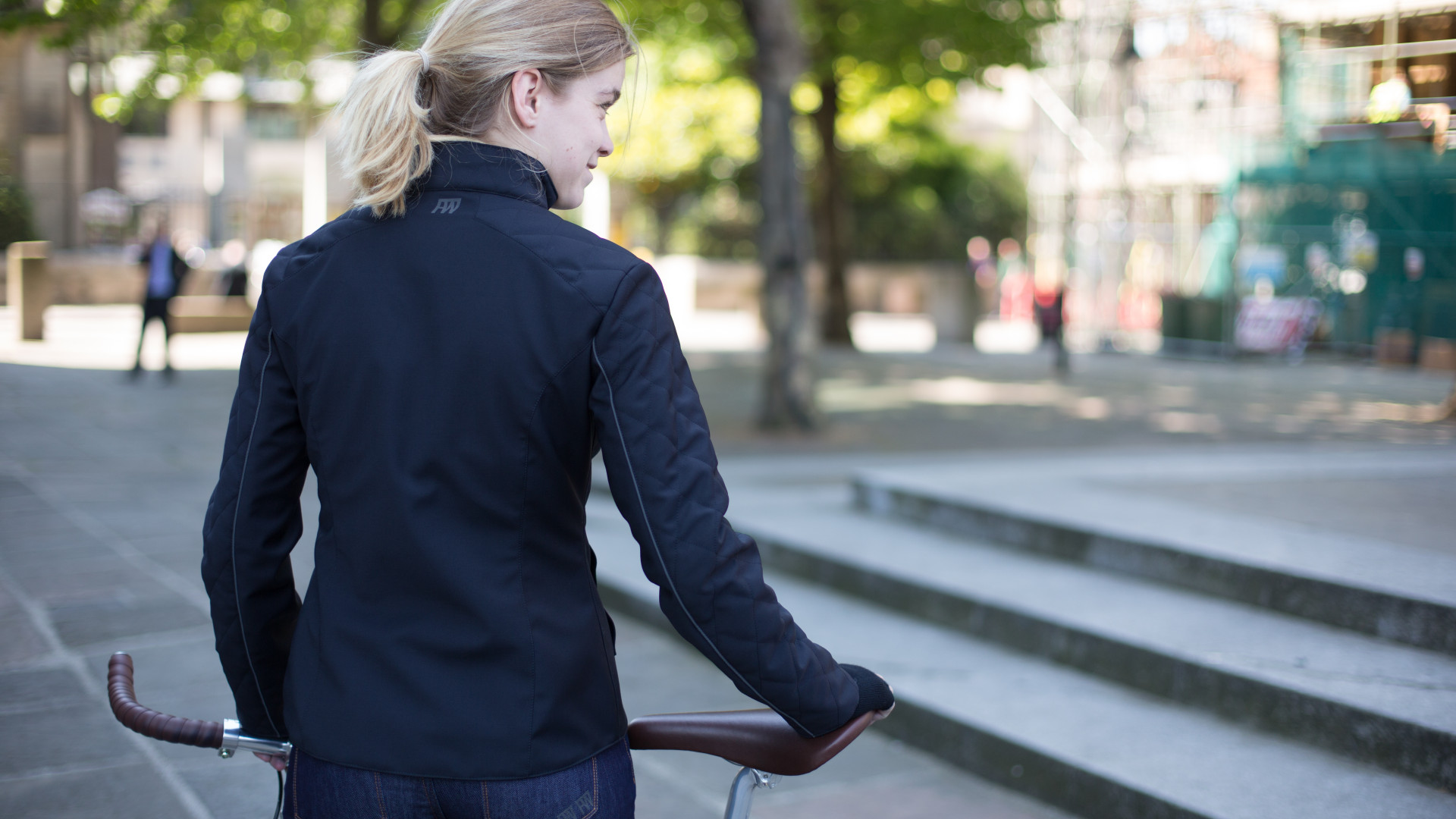 Female cyclist with her back to the camera wearing Fox Wilson clothing in the street